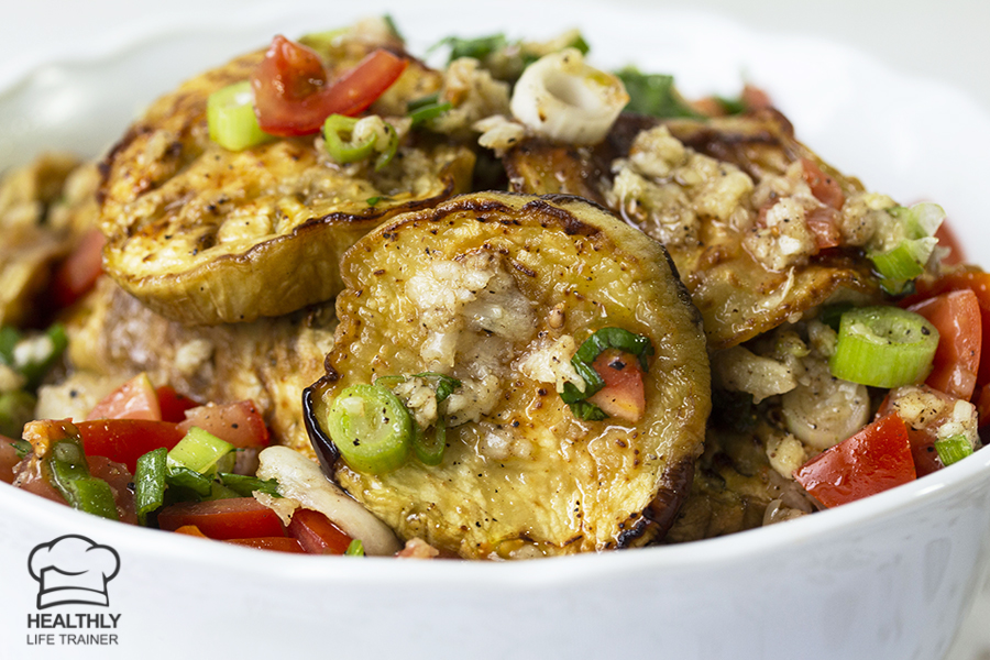 Mediterranean eggplant salad made with mixing baked or grilled eggplant, tomatoes, spring onion and drizzled with garlic, vinegar, olive oil.