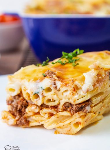 Baked pasta is layered with a well-seasoned beef mixture and topped with creamy bechamel sauce