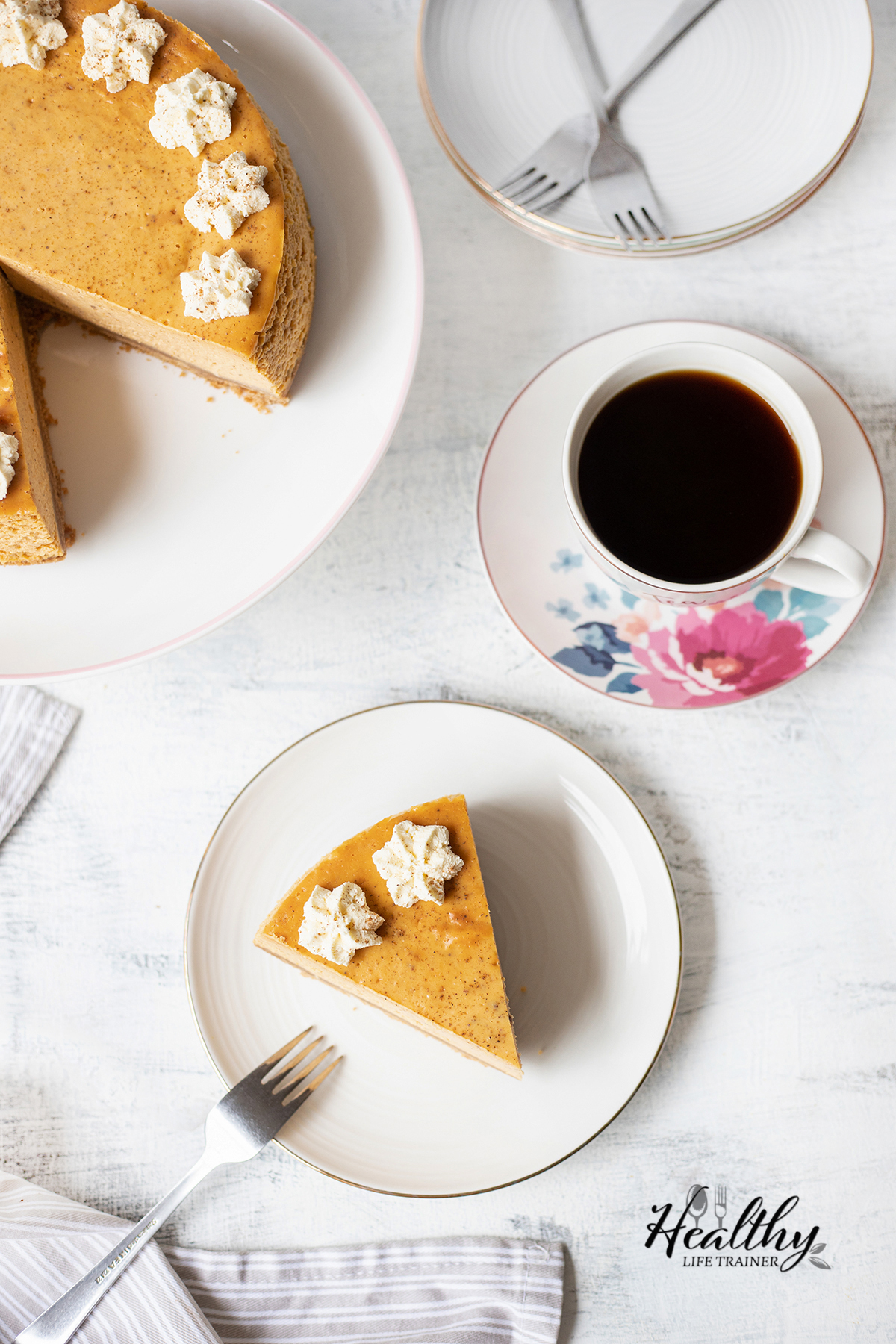 a cup of coffee and two plates of Pumpkin Cheesecake and a fork