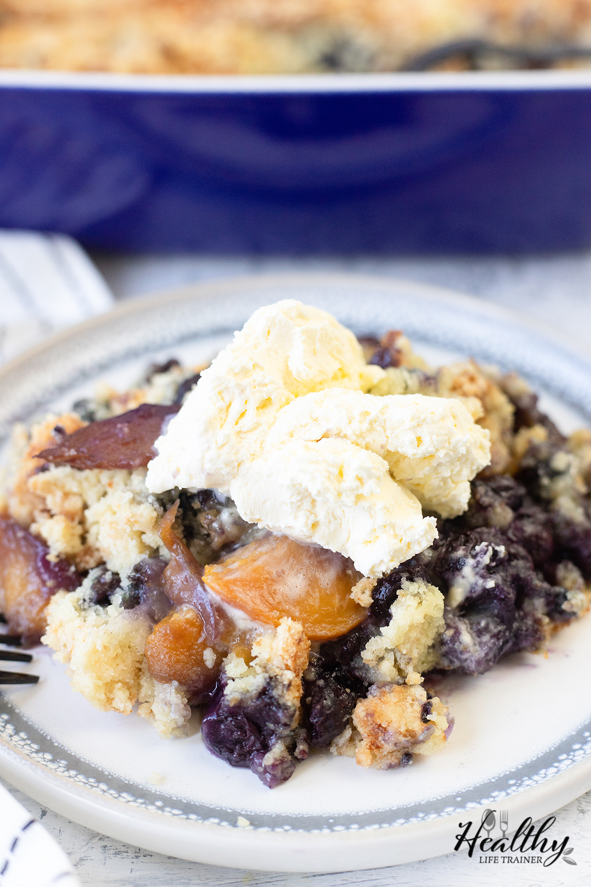 peach and blueberry cake topped with whipped cream