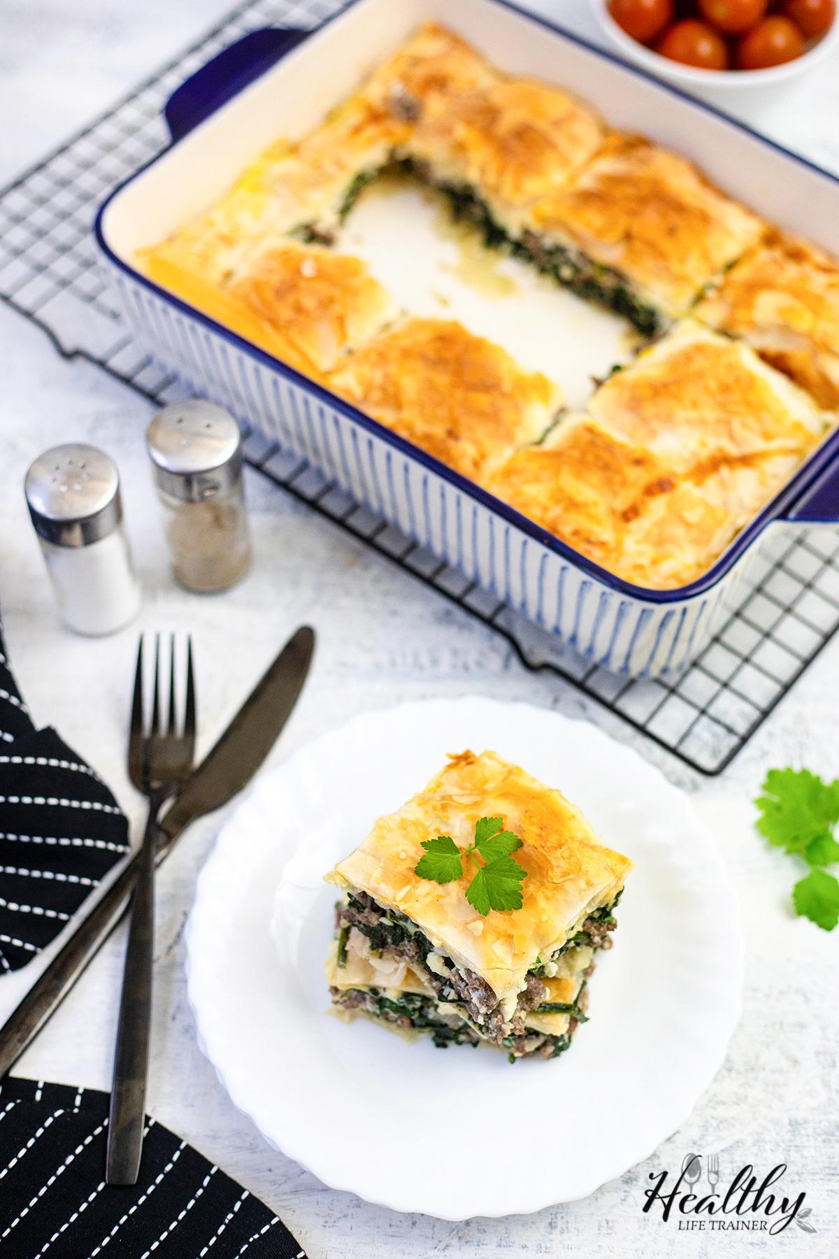 Spanakopita in a baking dish #spanakopitarecipe #spanakopitapie #spinachpie #dinnerpie #mediterraneanrecipe