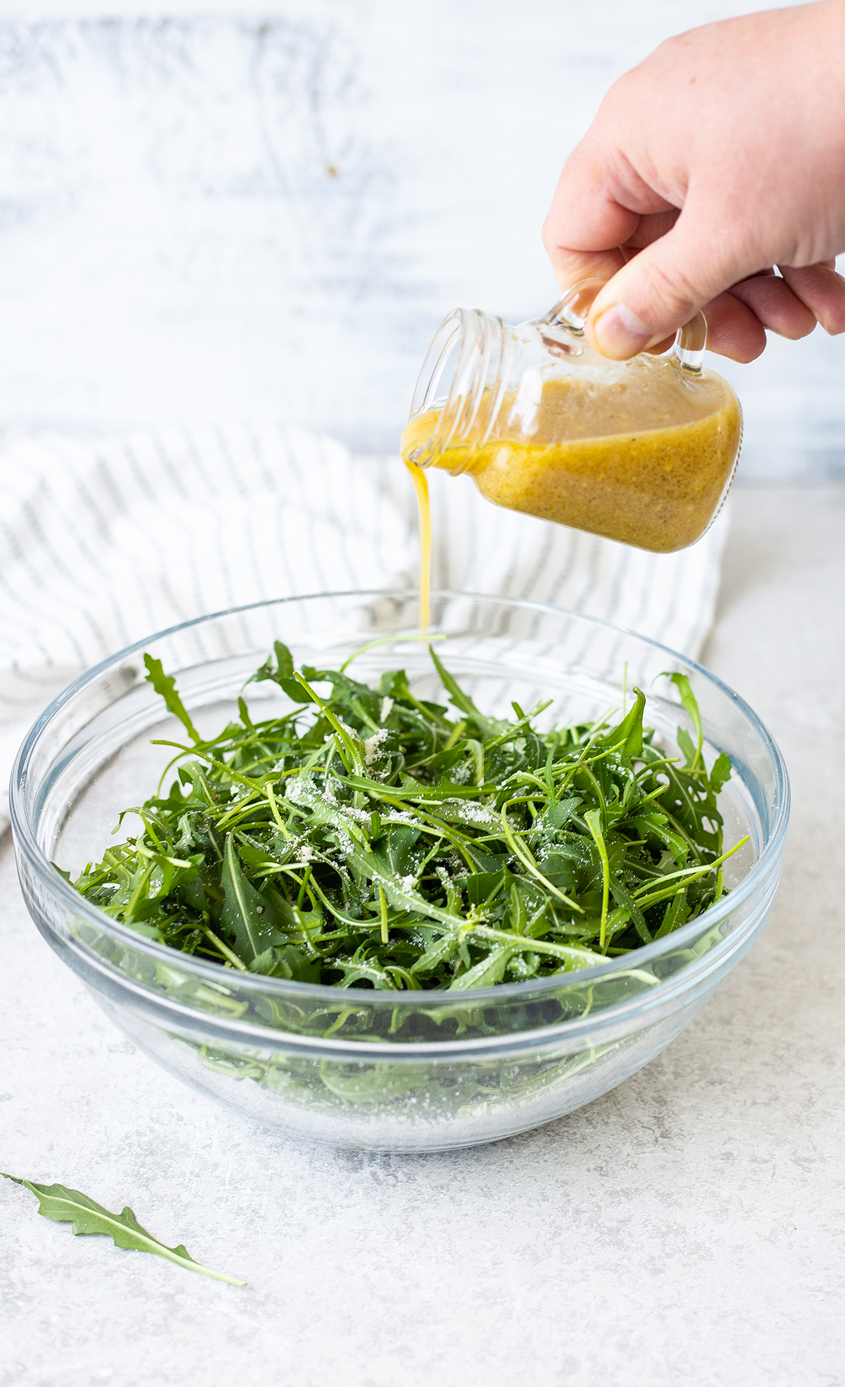 Pouring the Vinaigrette over the salad