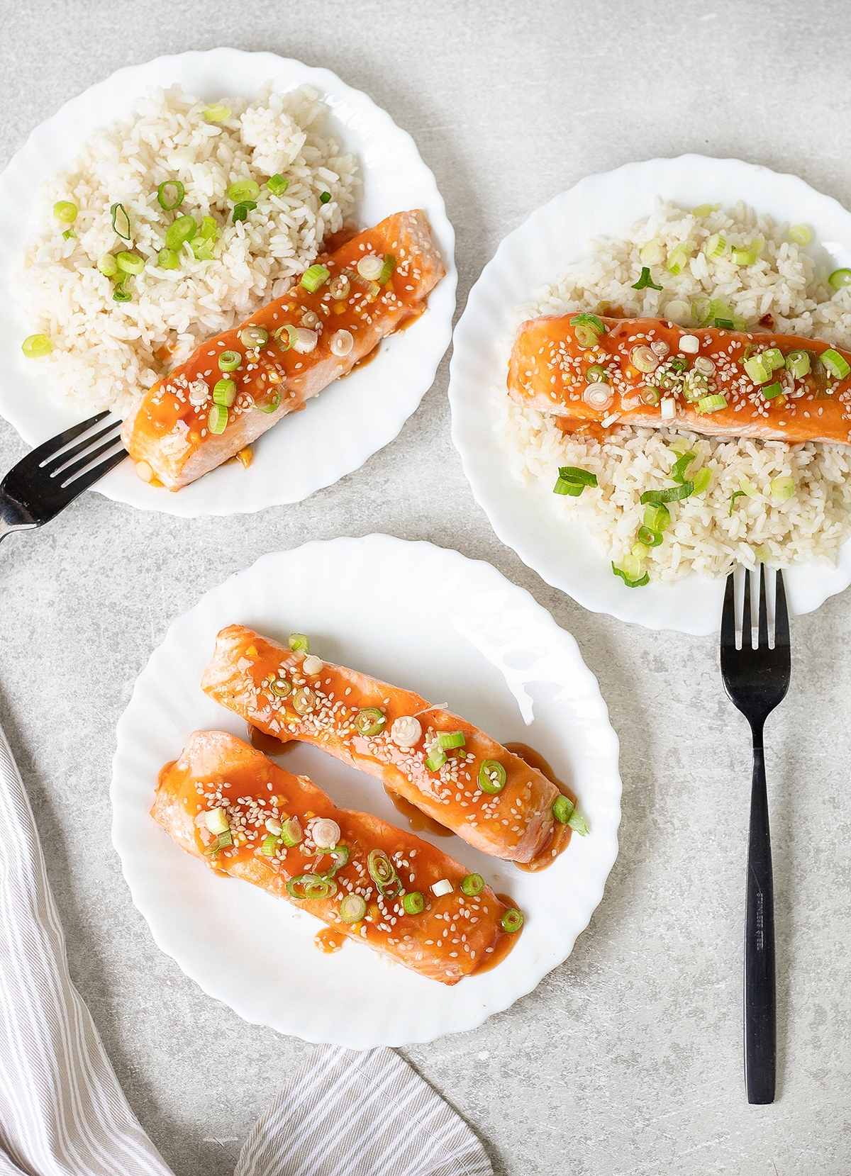 three plates of white rice topped with salmon
